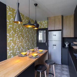 Cette image montre une grand cuisine design fermée avec une crédence noire, un électroménager en acier inoxydable, un îlot central, un sol gris, un évier 2 bacs, un placard à porte plane, des portes de placard noires, un plan de travail en bois et un plan de travail beige.