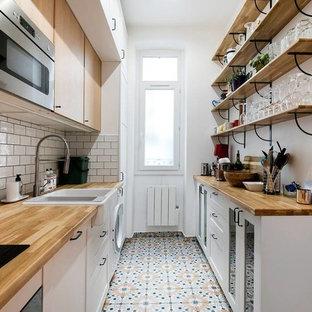 Idée de décoration pour une cuisine parallèle nordique avec un évier de ferme, un placard à porte plane, des portes de placard en bois clair, un plan de travail en bois, une crédence blanche, une crédence en carrelage métro et un sol multicolore.