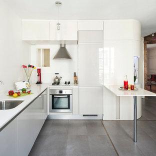 Foto de cocina en L, actual, de tamaño medio, abierta, con península, fregadero bajoencimera, puertas de armario blancas y suelo gris