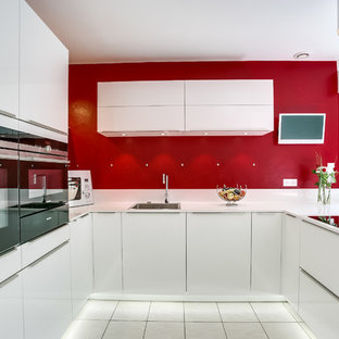 Mid-sized contemporary eat-in kitchen inspiration - Eat-in kitchen - mid-sized contemporary u-shaped eat-in kitchen idea in Paris with an undermount sink, flat-panel cabinets, white cabinets, red backsplash and white appliances