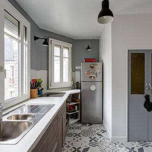 Cette image montre une cuisine linéaire design fermée et de taille moyenne avec un évier 2 bacs, un placard à porte plane, des portes de placard en bois brun, aucun îlot, un plan de travail en stratifié, une crédence blanche, une crédence en fenêtre, un électroménager en acier inoxydable, un sol en carreaux de ciment, un sol gris et un plan de travail blanc.
