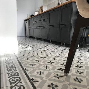 モンペリエの小さいミッドセンチュリースタイルのおしゃれなキッチン (タイルカウンター、セメントタイルの床、アンダーカウンターシンク、インセット扉のキャビネット、黒いキャビネット、グレーのキッチンパネル、磁器タイルのキッチンパネル、シルバーの調理設備の、アイランドなし、マルチカラーの床、茶色いキッチンカウンター) の写真