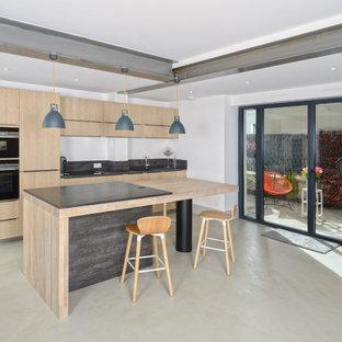 Inspiration pour une cuisine design avec un placard à porte plane, des portes de placard en bois clair, un électroménager noir, un îlot central et un sol beige.