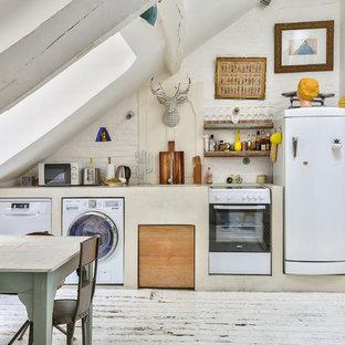Idée de décoration pour une cuisine américaine linéaire nordique avec un évier encastré, un électroménager blanc, un sol en bois peint, aucun îlot, un sol blanc et un plan de travail beige.