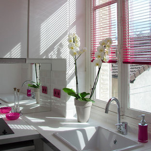 Kleine, Geschlossene Moderne Küche ohne Insel in L-Form mit Unterbauwaschbecken, flächenbündigen Schrankfronten, hellen Holzschränken, Laminat-Arbeitsplatte, Küchenrückwand in Weiß, Rückwand aus Spiegelfliesen und Vinylboden in Sonstige