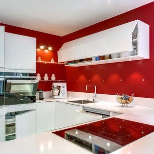 Modern inredning av ett mellanstort kök, med en undermonterad diskho, släta luckor, vita skåp, rosa stänkskydd och vita vitvaror