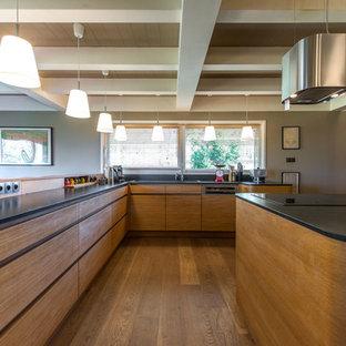 Große Nordische Wohnküche in U-Form mit Unterbauwaschbecken, hellen Holzschränken, Granit-Arbeitsplatte, Küchenrückwand in Schwarz, Küchengeräten aus Edelstahl, hellem Holzboden, Kücheninsel und schwarzer Arbeitsplatte in Lyon
