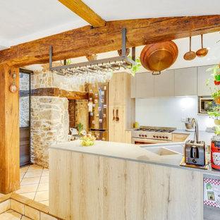 Cette photo montre une cuisine ouverte nature en U de taille moyenne avec un évier 2 bacs, un placard à porte plane, des portes de placard en bois clair, un plan de travail en surface solide, un sol en carreau de terre cuite, un sol marron, un plan de travail beige, un électroménager en acier inoxydable, une péninsule et un plafond en poutres apparentes.