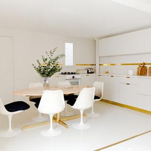 パリの大きいモダンスタイルのおしゃれなキッチン (アンダーカウンターシンク、インセット扉のキャビネット、ベージュのキャビネット、コンクリートカウンター、ベージュキッチンパネル、白い調理設備、コンクリートの床、アイランドなし、ベージュの床、ベージュのキッチンカウンター) の写真