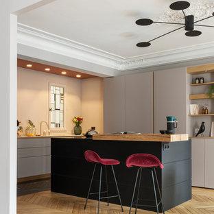 Exemple d'une cuisine tendance en L avec un évier encastré, un placard à porte plane, des portes de placard grises, une crédence beige, un électroménager encastrable, un sol en bois clair, un îlot central et un sol beige.
