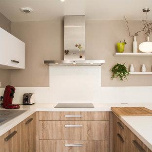 Imagen de cocina comedor en U, minimalista, pequeña, con fregadero de un seno, salpicadero blanco, electrodomésticos de acero inoxidable, península y puertas de armario de madera clara