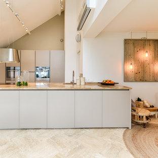 Cette photo montre une cuisine ouverte parallèle scandinave de taille moyenne avec un évier encastré, un placard à porte plane, des portes de placard grises et un îlot central.