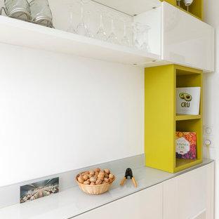 Aménagement d'une cuisine contemporaine fermée et de taille moyenne avec des portes de placard blanches et aucun îlot.