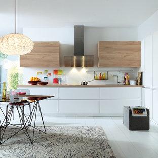 Idée de décoration pour une cuisine américaine design avec un évier posé, un placard à porte plane, des portes de placard blanches, un électroménager en acier inoxydable, un sol en bois peint, aucun îlot et un sol blanc.