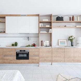 ナントの中くらいの北欧スタイルのおしゃれなキッチン (インセット扉のキャビネット、シングルシンク、中間色木目調キャビネット、白いキッチンパネル、黒い調理設備、セラミックタイルの床、アイランドなし、ベージュの床、白いキッチンカウンター) の写真