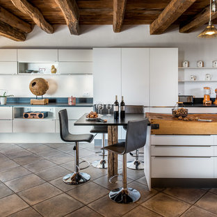 Réalisation d'une grand cuisine ouverte parallèle design avec un évier 1 bac, des portes de placard blanches, un plan de travail en granite, une crédence noire, un électroménager encastrable, un îlot central, un sol gris, un placard à porte plane et un plan de travail bleu.