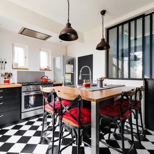 パリの中サイズのインダストリアルスタイルのおしゃれなキッチン (ダブルシンク、シェーカースタイル扉のキャビネット、黒いキャビネット、木材カウンター、白いキッチンパネル、サブウェイタイルのキッチンパネル、シルバーの調理設備の、セラミックタイルの床、黒い床、茶色いキッチンカウンター) の写真