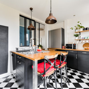 Design ideas for a mid-sized industrial galley separate kitchen in Paris with a double-bowl sink, black cabinets, wood benchtops, white splashback, a peninsula, shaker cabinets, subway tile splashback, stainless steel appliances, ceramic floors, black floor and brown benchtop.