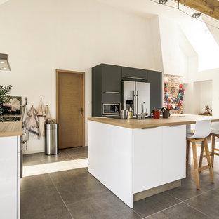 Cette photo montre une cuisine américaine scandinave en L de taille moyenne avec des portes de placard blanches, un plan de travail en stratifié, une crédence en carreau de ciment, un électroménager en acier inoxydable et un îlot central.