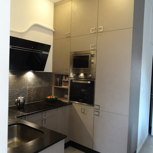 This is an example of a small industrial u-shaped open plan kitchen in Marseille with a single-bowl sink, beaded inset cabinets, brown cabinets, quartzite benchtops, grey splashback, slate splashback, stainless steel appliances, ceramic floors, no island, grey floor and black benchtop.