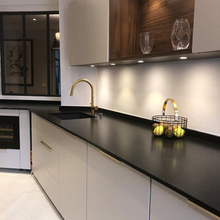 Photo of a mid-sized contemporary galley separate kitchen in Paris with an integrated sink, beaded inset cabinets, beige cabinets, granite benchtops, white splashback, ceramic floors, beige floor and black benchtop.