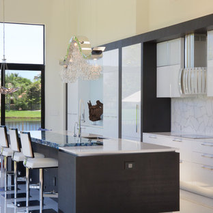 This is an example of an expansive modern galley open plan kitchen in Paris with an undermount sink, open cabinets, white cabinets, quartzite benchtops, white splashback, glass tile splashback, white appliances and with island.