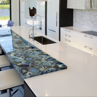 Photo of an expansive contemporary galley open plan kitchen in Paris with an undermount sink, open cabinets, white cabinets, quartzite benchtops, white splashback, glass tile splashback, white appliances and with island.