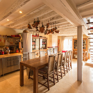 Inspiration for a large country single-wall open plan kitchen in Paris with open cabinets, medium wood cabinets, wood benchtops, beige splashback and travertine splashback.