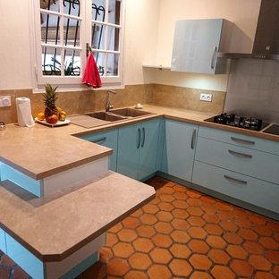 他の地域の中サイズのモダンスタイルのおしゃれなキッチン (ダブルシンク、緑のキャビネット、ラミネートカウンター、ベージュキッチンパネル、カラー調理設備、テラコッタタイルの床、アイランドなし、赤い床) の写真
