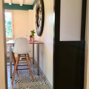パリの中サイズのインダストリアルスタイルのおしゃれなキッチン (アンダーカウンターシンク、フラットパネル扉のキャビネット、白いキャビネット、ラミネートカウンター、ベージュキッチンパネル、木材のキッチンパネル、シルバーの調理設備の、セメントタイルの床、マルチカラーの床、ベージュのキッチンカウンター) の写真