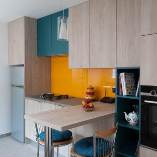 Exemple d'une cuisine parallèle tendance fermée et de taille moyenne avec un évier intégré, un placard à porte affleurante, des portes de placard en bois clair, un plan de travail en stratifié, une crédence orange, une crédence en feuille de verre, un électroménager en acier inoxydable, un sol en carrelage de céramique, aucun îlot, un sol gris et un plan de travail gris.