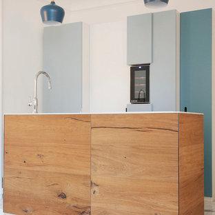 Idées déco pour une cuisine ouverte parallèle contemporaine de taille moyenne avec des portes de placard bleues et un îlot central.