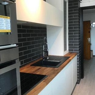 ランスの小さいコンテンポラリースタイルのおしゃれなキッチン (シングルシンク、白いキャビネット、木材カウンター、黒いキッチンパネル、レンガのキッチンパネル、シルバーの調理設備、アイランドなし) の写真