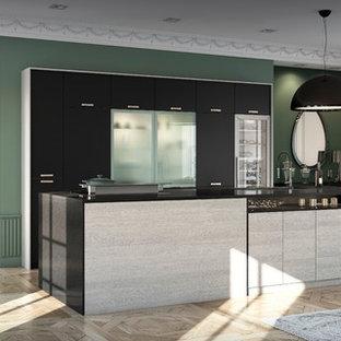 Réalisation d'une cuisine américaine parallèle tradition avec un placard à porte plane, des portes de placard noires, un plan de travail en quartz et un îlot central.