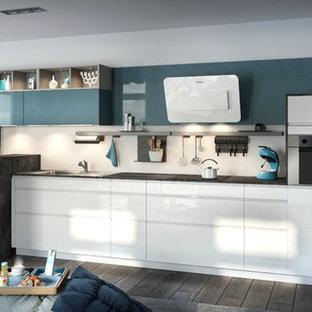 Exemple d'une cuisine linéaire tendance avec un placard à porte affleurante et des portes de placard blanches.
