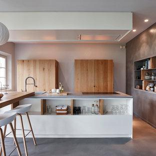 Cette image montre une grande cuisine américaine parallèle design avec des portes de placard en bois brun, un plan de travail en béton, béton au sol, 2 îlots, un évier posé et un placard sans porte.