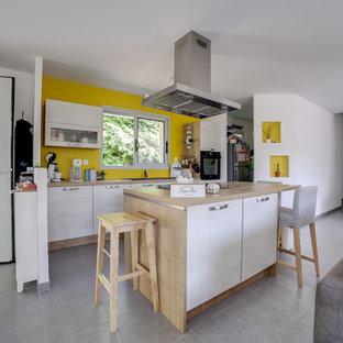 他の地域のコンテンポラリースタイルのおしゃれなキッチン (アンダーカウンターシンク、白いキャビネット、木材カウンター、黄色いキッチンパネル、黒い調理設備、グレーの床、ベージュのキッチンカウンター) の写真