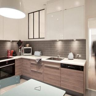 Idée de décoration pour une cuisine américaine design en L de taille moyenne avec un évier 1 bac, des portes de placard en bois clair, une crédence grise, un électroménager encastrable, un sol en carrelage de céramique et aucun îlot.