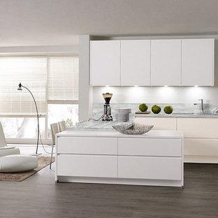 Modern inredning av ett mycket stort kök med öppen planlösning, med vita skåp, bänkskiva i onyx, grått stänkskydd, integrerade vitvaror, laminatgolv och brunt golv