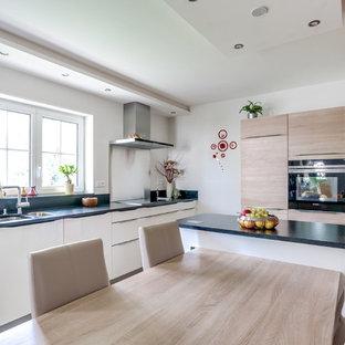 Cette image montre une cuisine américaine design en L de taille moyenne avec un évier encastré, un placard à porte plane, des portes de placard en bois clair, une crédence noire et un îlot central.