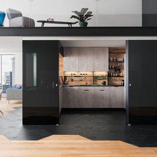 Idée de décoration pour une cuisine minimaliste en U avec un évier posé, un placard à porte plane, des portes de placard grises, une crédence beige, une crédence en bois, une péninsule, un sol noir et un plan de travail noir.