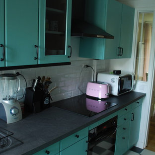 Photo of a small midcentury galley separate kitchen in Paris with a double-bowl sink, raised-panel cabinets, green cabinets, laminate benchtops, white splashback, subway tile splashback, black appliances, ceramic floors and no island.