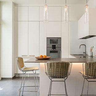 Idée de décoration pour une cuisine américaine design en L de taille moyenne avec un évier 1 bac, des portes de placard blanches, une crédence blanche, une crédence en feuille de verre, un électroménager en acier inoxydable, un sol en carrelage de céramique et une péninsule.