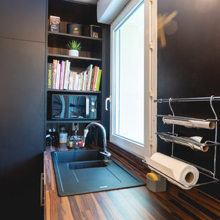 This is an example of a small contemporary l-shaped open plan kitchen in Paris with a single-bowl sink, beaded inset cabinets, black cabinets, wood benchtops, black splashback, timber splashback, black appliances, light hardwood floors, with island, beige floor and beige benchtop.