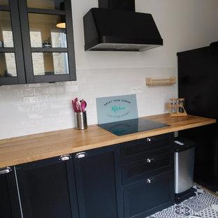 他の地域の中サイズのインダストリアルスタイルのおしゃれなキッチン (ドロップインシンク、ガラス扉のキャビネット、黒いキャビネット、木材カウンター、白いキッチンパネル、セラミックタイルのキッチンパネル、セメントタイルの床、黒い床) の写真