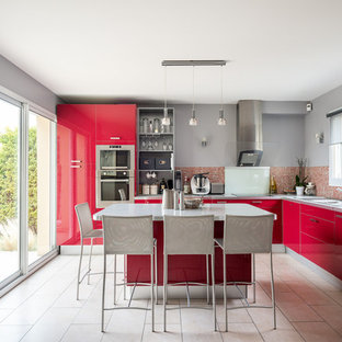 Inspiration pour une grande cuisine design en L avec un évier 2 bacs, un placard à porte plane, des portes de placard rouges, un plan de travail en stratifié, une crédence rouge, une crédence en mosaïque, un électroménager en acier inoxydable, un îlot central, un sol beige et un plan de travail gris.
