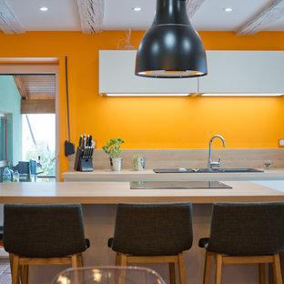 Réalisation d'une cuisine ouverte design en L avec des portes de placard blanches, un plan de travail en stratifié, un îlot central, un évier posé, un placard à porte plane, une crédence en bois et un sol en carreau de terre cuite.