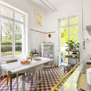 Réalisation d'une cuisine américaine linéaire champêtre avec un évier 2 bacs, un plan de travail en inox, une crédence blanche, un sol rouge et un plan de travail gris.