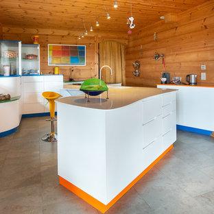 Idées déco pour une cuisine éclectique avec un placard à porte plane, des portes de placard blanches, un îlot central et un sol gris.