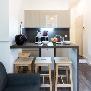 Réalisation d'une cuisine ouverte linéaire design avec un placard à porte plane, des portes de placard beiges, une crédence noire, un électroménager blanc, un sol en bois foncé, aucun îlot, un sol marron et un plan de travail noir.